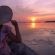 Female Tourist in Hat Watching Sunrise Riding Boat in Lake at Thale Noi Waterfowl Reserve, Thailand - VideoHive Item for Sale