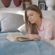 Girl Reads a Book Lying in Bed - VideoHive Item for Sale