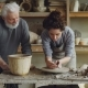 Caring Grandfather Experienced Potter Is Teaching Yong Girl How To Work with Clay on Potter's Wheel - VideoHive Item for Sale