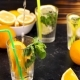 Pouring Water in a Glass with Slices of Oranges Next To Glasses with Lemonade - VideoHive Item for Sale