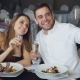 Attractive Loving Couple Is Taking Selfie with Champagne Glasses Using Smartphone While Having - VideoHive Item for Sale