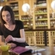 A Young Girl Drinks Coffee and Reads a Fashion Magazine in a Cafe or Restaurant, Woman Reading - VideoHive Item for Sale