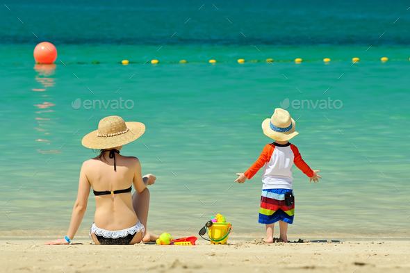 Two year old toddler playing with mother on beach - Stock Photo - Images