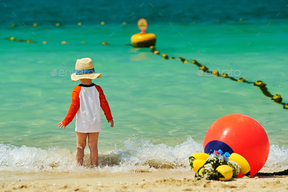 Two year old toddler boy walking on beach - Stock Photo - Images
