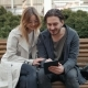 Couple Sitting on Public Bench and Using Tablet, Man and Woman Students Near University Campus - VideoHive Item for Sale