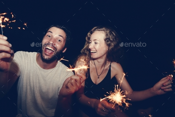 Happy couple with sparklers in the night - Stock Photo - Images