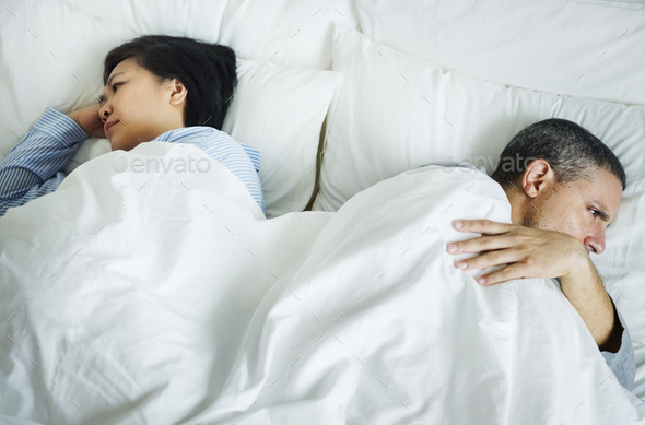 Couple on a bed having a problem - Stock Photo - Images