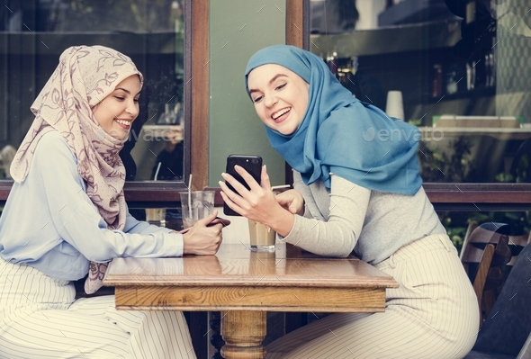 Islamic friends talking and looking on the smart phone - Stock Photo - Images