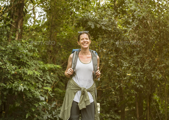 Cheerful female backpacker in the forest - Stock Photo - Images