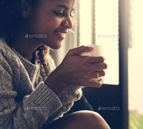 Woman having a warm cup of coffee - Stock Photo - Images