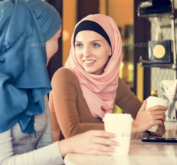 Islamic women friends enjoying and talking in the coffee shop - Stock Photo - Images