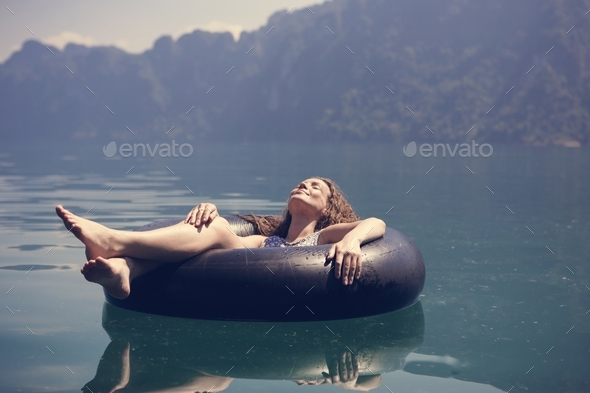 Woman relaxing on a floating ring - Stock Photo - Images