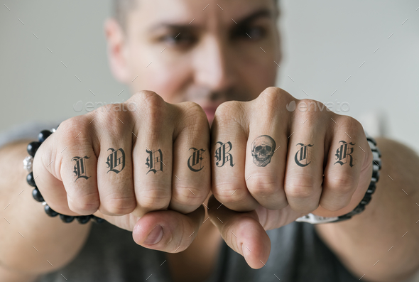 Closeup of knucle tattoos of a man - Stock Photo - Images