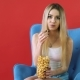 Pretty Young Woman Sitting on a Sofa with Her Legs Crossed, Eating Popcorn and Watching TV. - VideoHive Item for Sale