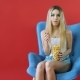 Pretty Young Woman Sitting on a Sofa with Her Legs Crossed, Eating Popcorn and Watching TV - VideoHive Item for Sale