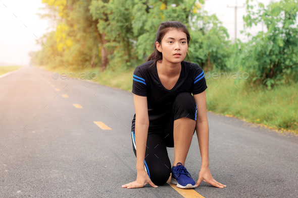 Girl is preparing to run on street - Stock Photo - Images