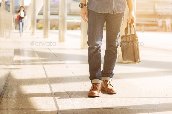Man holding leather bag in city - Stock Photo - Images