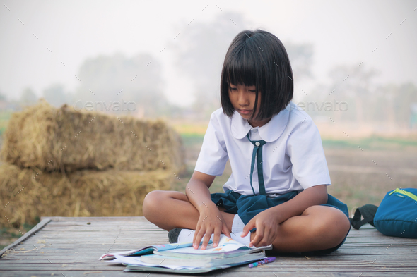 The girl reads a book on bamboo mat - Stock Photo - Images