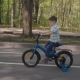 Little Boy Rides Bike Along the City Park. Small Bicyclist Riding Blue Bicycle - VideoHive Item for Sale