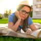 Girl in Glasses Reading Book Lying Down on a Blanket in the Park at Sunset - VideoHive Item for Sale