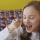 Happy Young Girl Eating Tasty Dessert and Smiling at Camera. Slowly - VideoHive Item for Sale