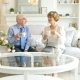 Happy Caucasian Couple of Retirement Age Are Spending Time Together Sitting at a Table and Drinking - VideoHive Item for Sale