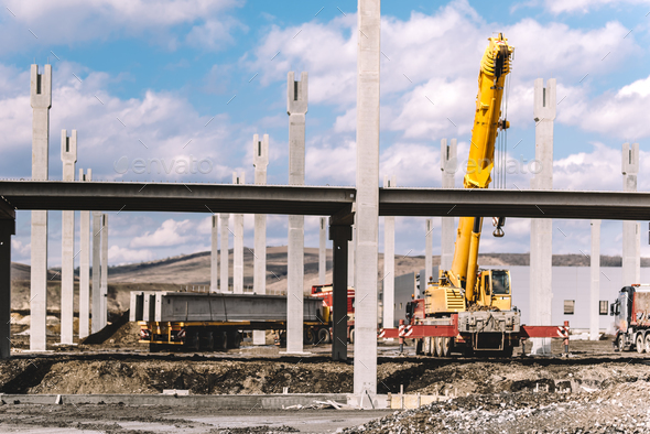 Industrial construction site with prefabricated concrete pillars, heavy duty crane, cargo and trucks - Stock Photo - Images
