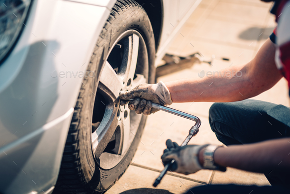 Tire maintenance, damaged car tyre or changing seasonal tires using wrench - Stock Photo - Images
