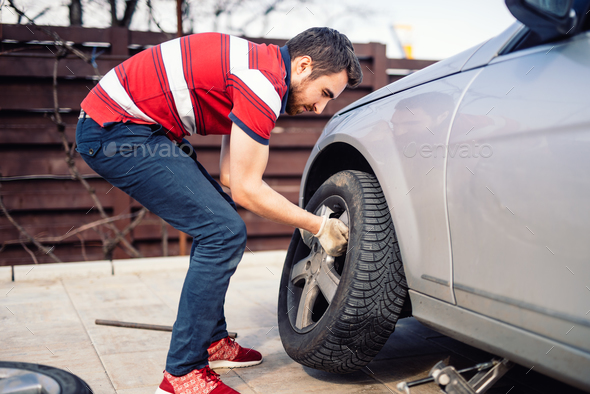 Potrait of young man changing seasonal tires, installing summer tires on automobile - Stock Photo - Images
