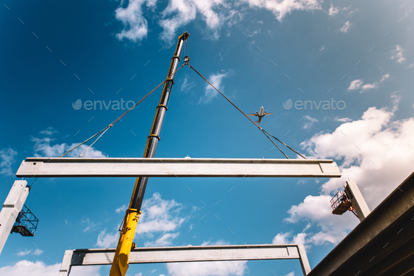 Construction site building assembly - crane lifting a precast concrete cement beam - Stock Photo - Images