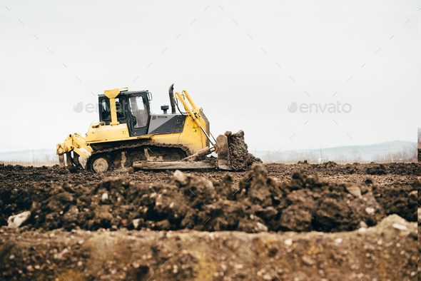 mini industrial bulldozer moving dirt and earth with scoop. Industrial details of landscaping - Stock Photo - Images