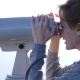 Woman Blond Traveler Looking Through a Telescope on Top of a Mountain - VideoHive Item for Sale
