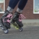 Women's Legs in Roller Skates Whirl Around on Asphalt in City - VideoHive Item for Sale