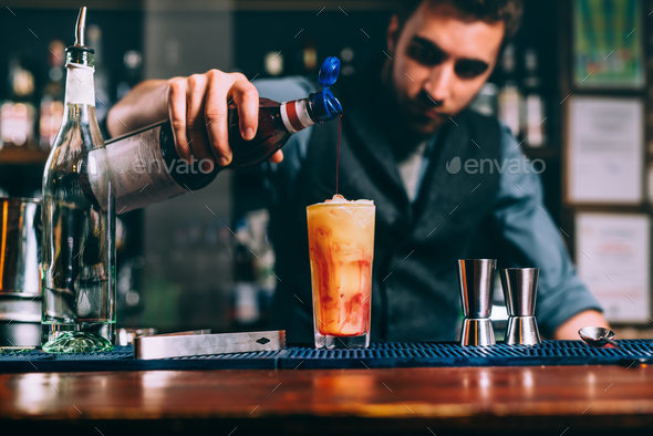 portrait of bartender pouring cherry syroup in orange summer cocktail. details of bar and restaurant Stock Photo by stockcentral