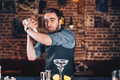 Lifestyle details with barman portrait using shaker and preparing cocktail at bar - PhotoDune Item for Sale
