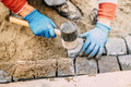 Construction worker placing stone tiles, cobblestone blocks in s - PhotoDune Item for Sale