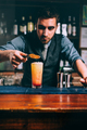 summer cocktail, orange with cherry and orange slice. Close up of handsome bartender at work - PhotoDune Item for Sale