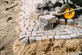 details of pavement road building with cobblestone blocks, wheelbarrow and level tools - PhotoDune Item for Sale