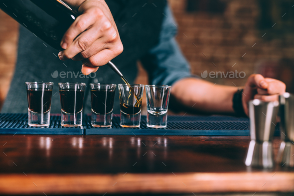 Bartender pouring strong alcoholic drink into small glasses on bar counter - Stock Photo - Images