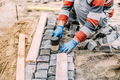 construction worker using industrial tools for stone pavement. granite blocks install details - PhotoDune Item for Sale