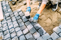 industrial construction worker, handyman using cobblestone granite stones for creating walking path - PhotoDune Item for Sale