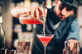 barman preparing and pouring red cocktail in martini class.  - PhotoDune Item for Sale