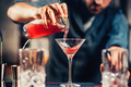 Close up details of barman pouring vodka cosmopolitan cocktail in martini glass - PhotoDune Item for Sale