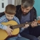 Concentrated Child Is Playing Guitar with His Father Experienced Guitarist, Adjusting Musical - VideoHive Item for Sale