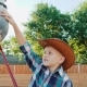 Young Little Cowboy Caressing a Pretty White Horse on the Area - VideoHive Item for Sale