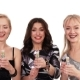 Three Beautiful Cheerful Girls Blow up Crackers with Confetti in Studio on White Background - VideoHive Item for Sale