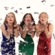 3 Beautiful Girls in Bright Dresses Blowing on Confetti at a Party in a Studio on a White Background - VideoHive Item for Sale