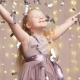 Beautiful Blonde Girl Throws Silvery Confetti on the Background of a Blinking Garland - VideoHive Item for Sale
