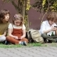 Two Brothers and a Sister Use Smartphones Sitting on the Grass. Socializing in Social Networks - VideoHive Item for Sale