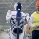 Cyborg Is Moving a Transporting Tool Along the Factory Unit While Being Regulated By a Male Worker - VideoHive Item for Sale